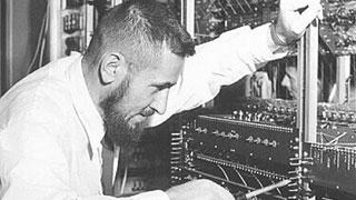 CUSTOM of man working on Silliac super computer