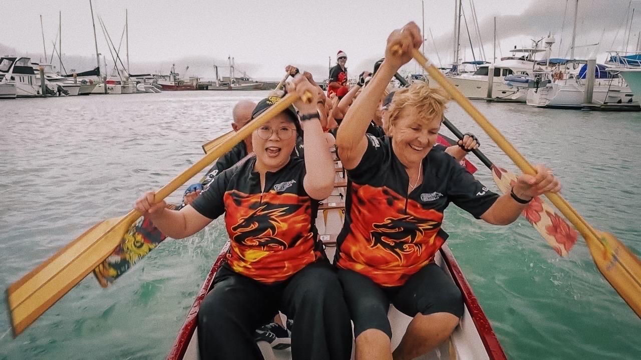 Jennifer Wong and the Hervey Bay Dragons paddling in a dragon boat.