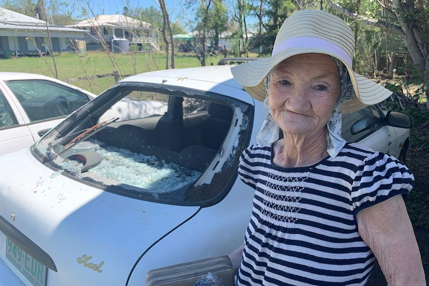 Rosewood resident Robyn McInnes stands next to a car with a smashed rear window after hailstorms.