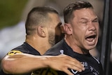 A Penrith NRL player screams out as he is hugged by a teammate after scoring a try against the Sydney Roosters.