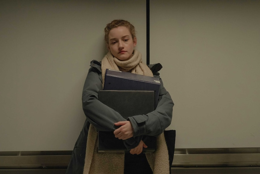 The actor Julia Garner in a scene from the film The Assistant as a downtrodden assistant, laden with folders, in a lift