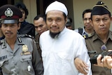 Militant cleric of Jamaah Islamiyah is escorted by security officers after a trial in this 2003 photo.