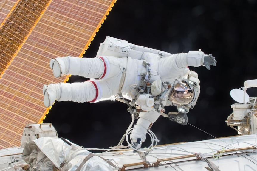 Scott Kelly floats sideways in space in an astronaut suit.
