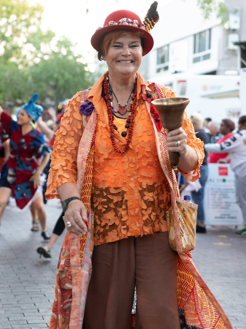 woman with hat leading a parade wearing town crier garb