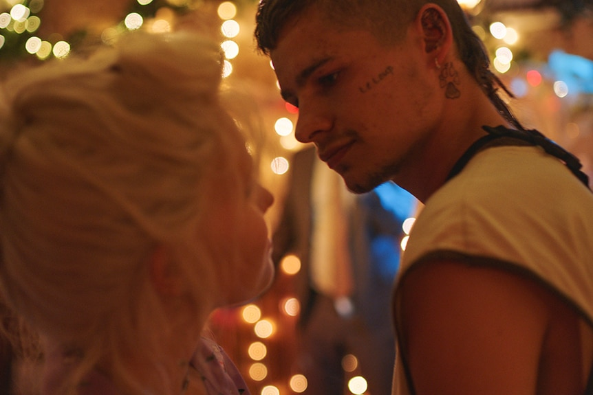 A young blonde girl and tattooed boy with rat tail stand close in party setting, behind them is out of focus fairy lights.