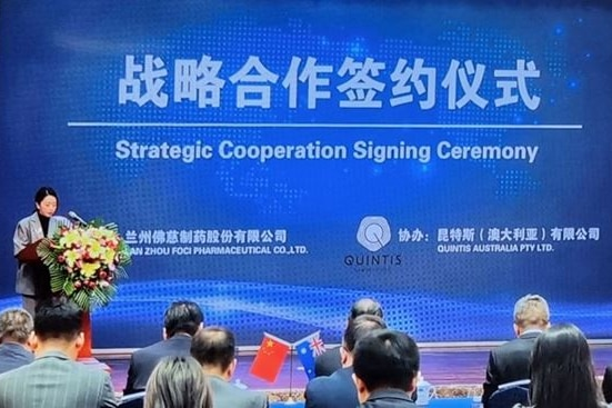 Photo of a signing ceremony in front of a blue sign with Chinese writing