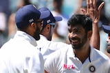 Jasprit Bumrah smiles and looks at his teammate as a group of men crowd around him
