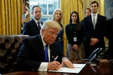 US President Donald Trump signs an executive order in the White House.