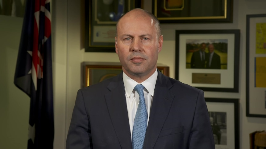 A man in a suit and blue tie stares into the camera. Behind him are portraits and the Australian flag.