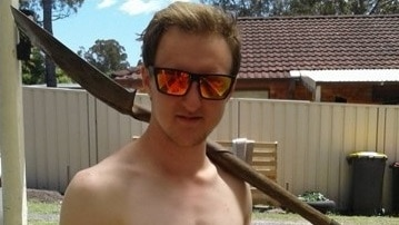 A shirtless young man wearing reflective sunglasses stands in a back yard with a shovel over his shoulder.
