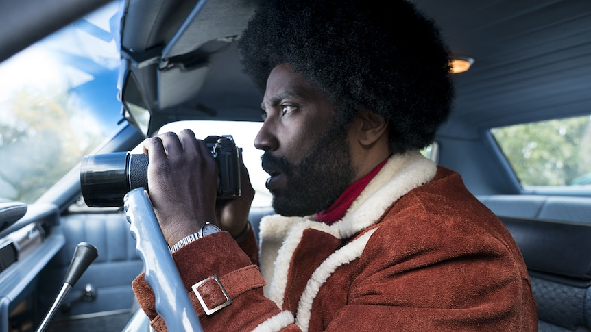 Colour close-up image of John David Washington holding binoculars and sitting in a car.
