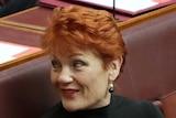 Senator Pauline Hanson looks over her shoulder in the Senate