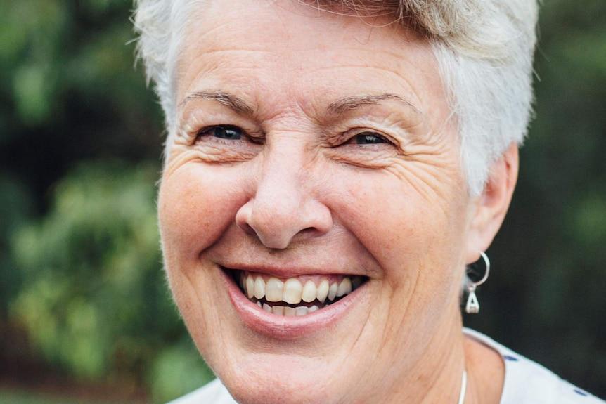 Edwina Aubin with grey hair and a green leafy background.