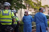 Two men in blue medical gowns and masks speak with two police officers.