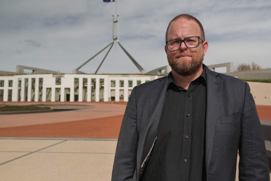 A man with glasses stands out the front of Parliament House.