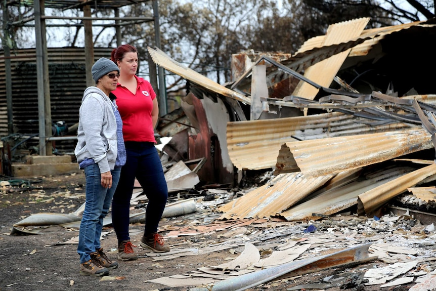 A woman in a red t-shirt and a woman in a beanie and cardigan stand among the ruins of a burnt house