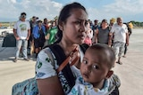 Mother and child wait to be evacuated in Indonesia