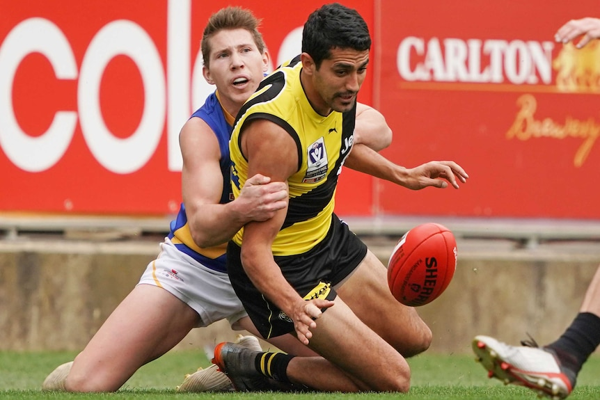 Marlion Pickett is tackled by a Williamstown seagulls player and looks at the ball as he falls to his knees
