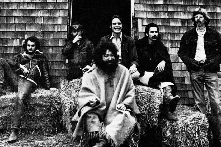Black and white image of six men from the band Grateful Dead lounging on haybales
