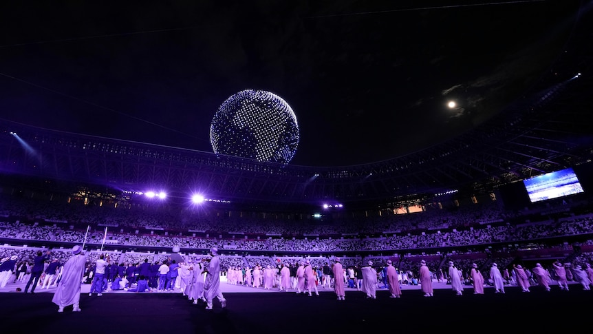 A globe rises above a stadium with people