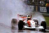 Ayrton Senna driving in the rain at Silverstone.