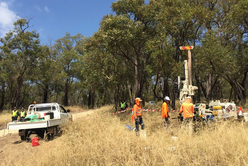 Workers stand around a drill rig in Bibra Lake, near a ute and two police officers.