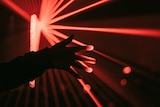 Picture of a hand with red laser lights behind it
