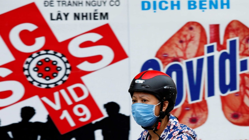 A woman wears a protective mask as she drives past a banner promoting prevention of COVID-19.