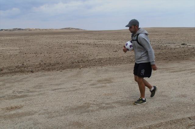 Matt Napier walking in the desert with a soccer ball under his arm.