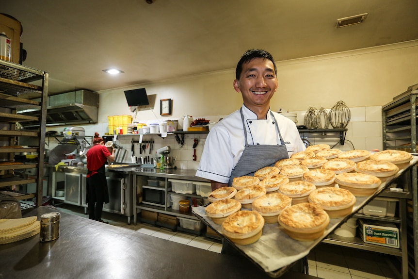 Chan Khun holding a tray of pies.