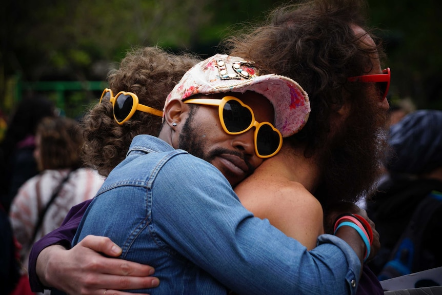 Man hugs another man while wearing heart-shaped sunglasses and a cap to depict how to choose the best sunscreen.