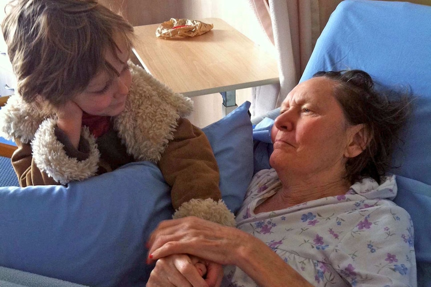 A woman lies in a nursing care bed while holding the hand of a young boy who has his hand on his face