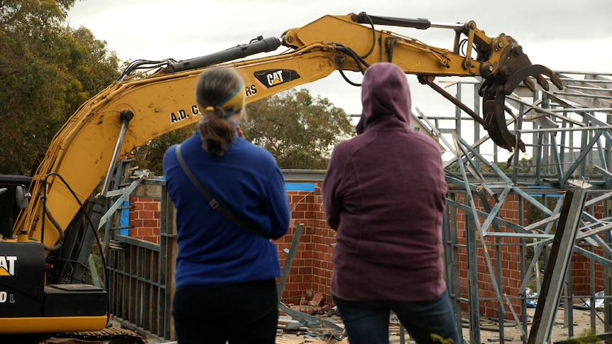 Two women with their backs turned with a digger demolishing a home in the background