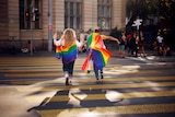 Two people hold a rainbow flag while crossing a street in Zurich