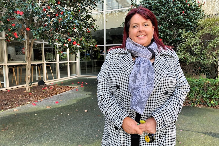 President of the Real Estate of Institute of Tasmania Mandy Welling stands in a courtyard.