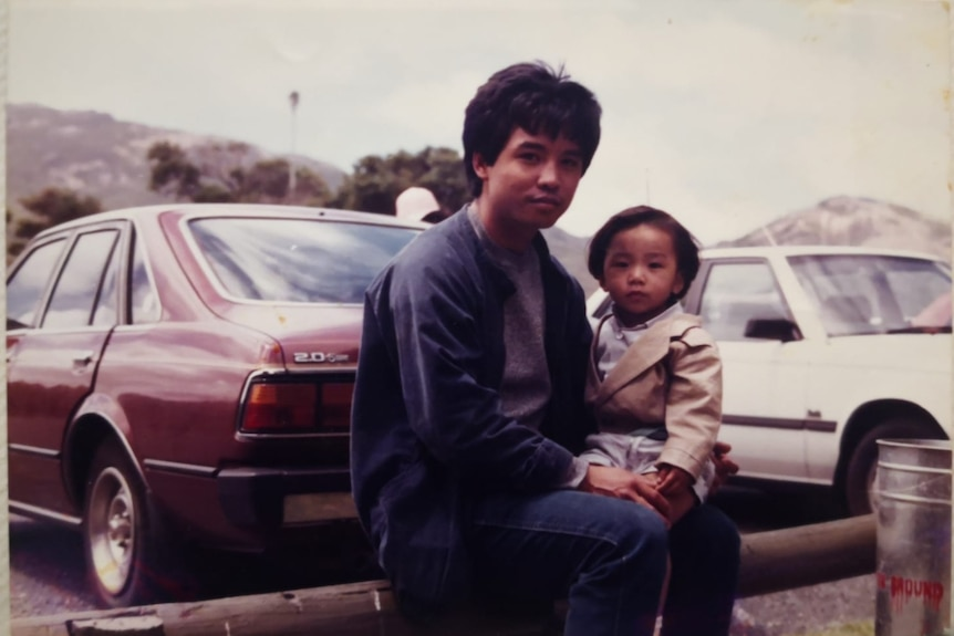 An old photo of a father and son posing near 1970s cars.