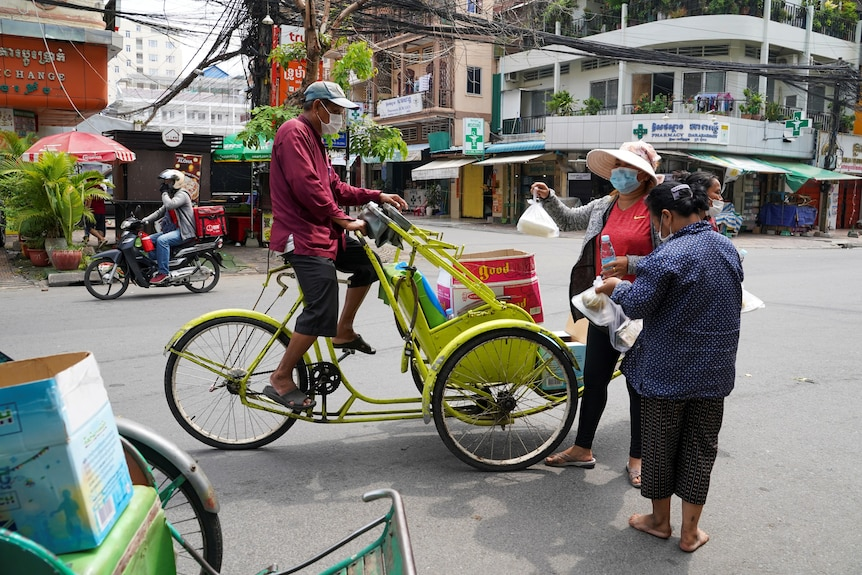 A man on a bike talking to two women holding plastic bags of food