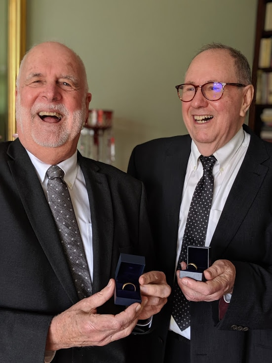 Father John Davis and Father Rob Whalley show off their wedding rings