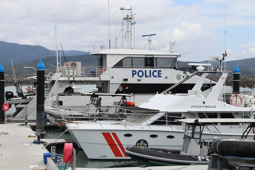 A large police boat moored in a marina.