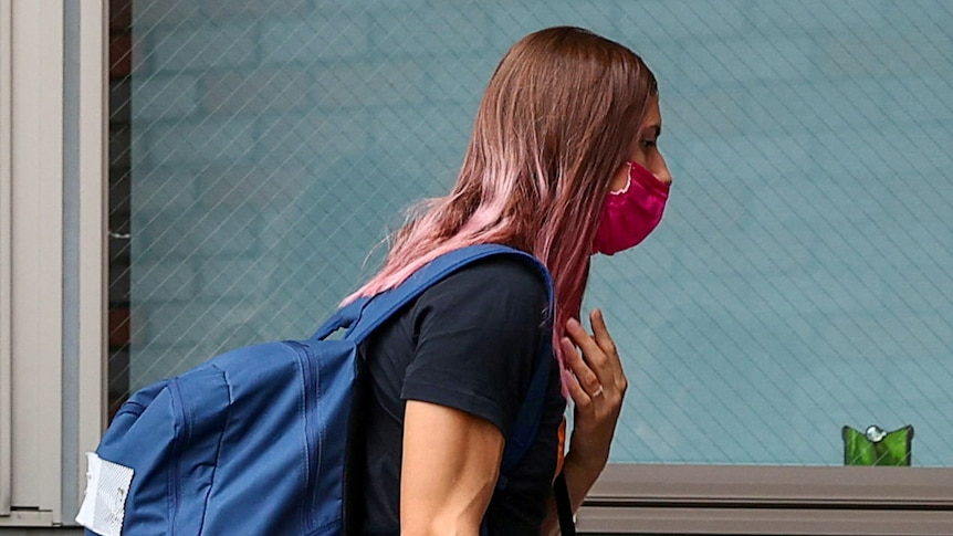 A woman with dyed pink hair wearing a backpack and face mask walks into a building.