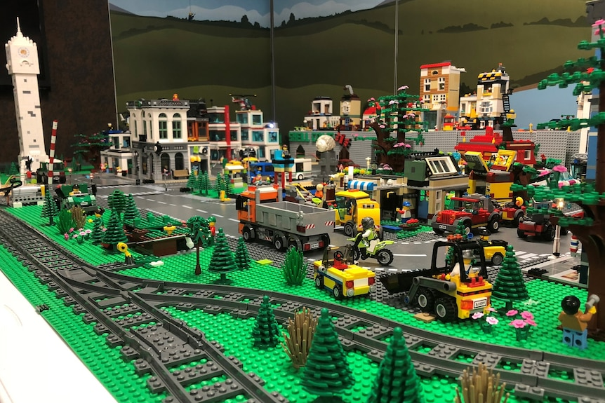 A model city made of Lego, complete with train tracks, cars and trucks, buildings and roads.