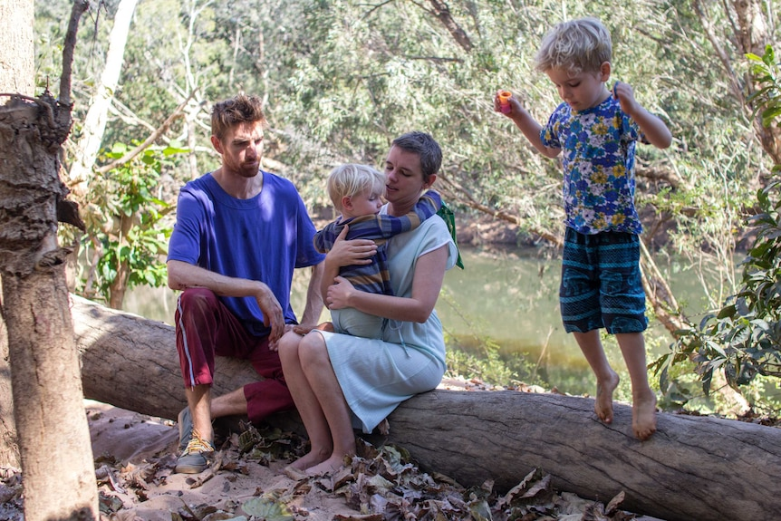 a man, a woman holding her child and a young boy on a log near a river.