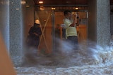 A man attempts to take a picture while being blown by strong winds and flood water in Hong Kong