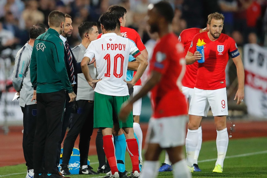 A team manager talks to a referee after an international game is halted because of racist abuse.