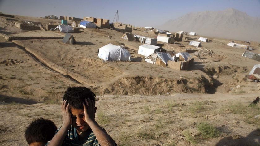 Afghan refugee children stand on the barren, dusty plains in Barikab, Afghanistan