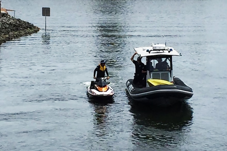 Police on a jetski and rubber inflatable search a Gold Coast canal for a missing kayaker.
