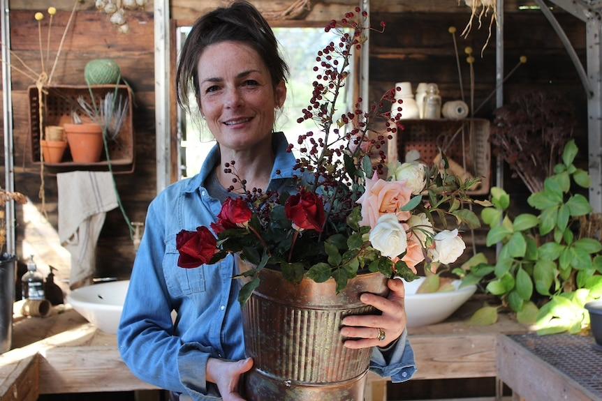 Organic flower grower Danielle White holding up a bouquet of flowers at her property.