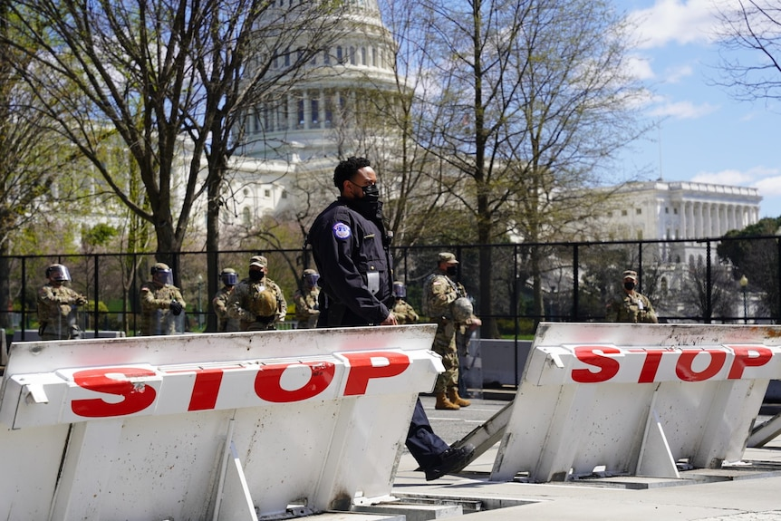 A police officer walks through two barricades painted with the word STOP in large red letters.