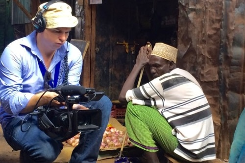 Cuddihy squats down while holding a camera, next to a man sitting on a stool outside a shop front.