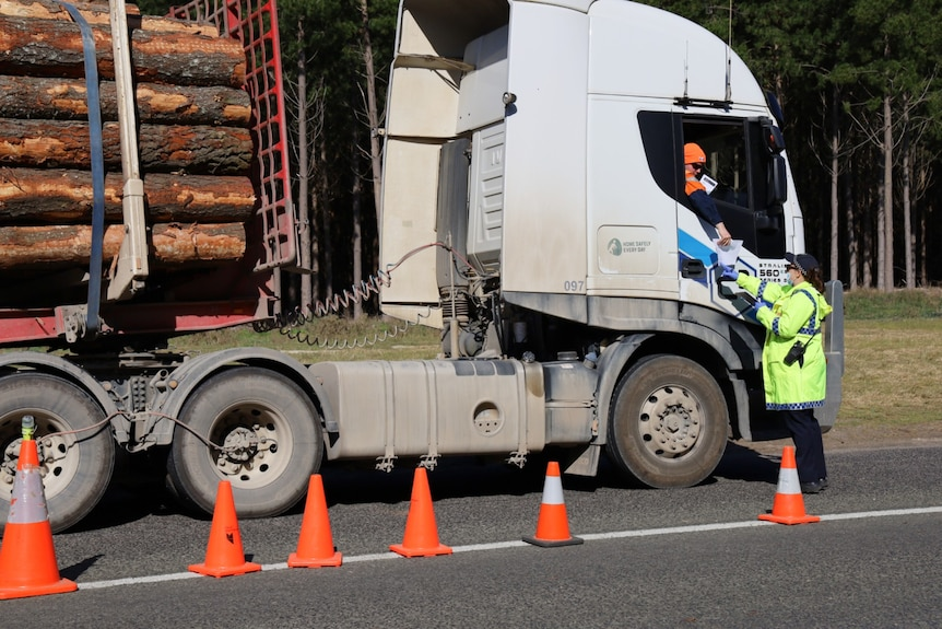 A police officer standing next to a forestry freight truck, the driver leaning out the window
